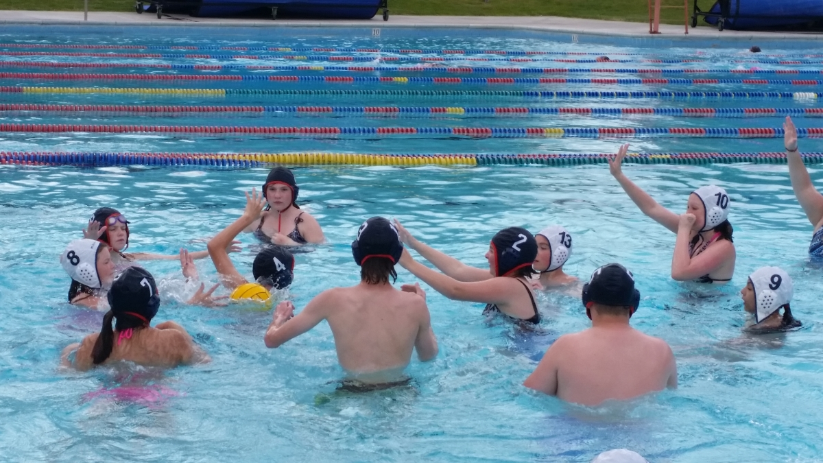 Students in a pool playing water polo