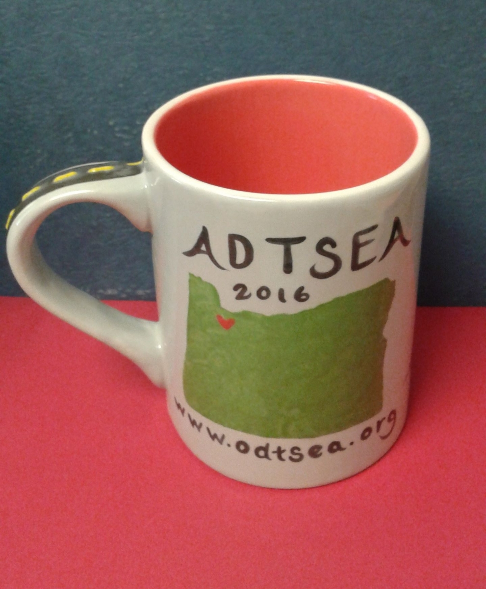 A hand painted tan mug with a road going up the handle, the map of Oregon on the body, with ADTSEA 2016 written along the top.