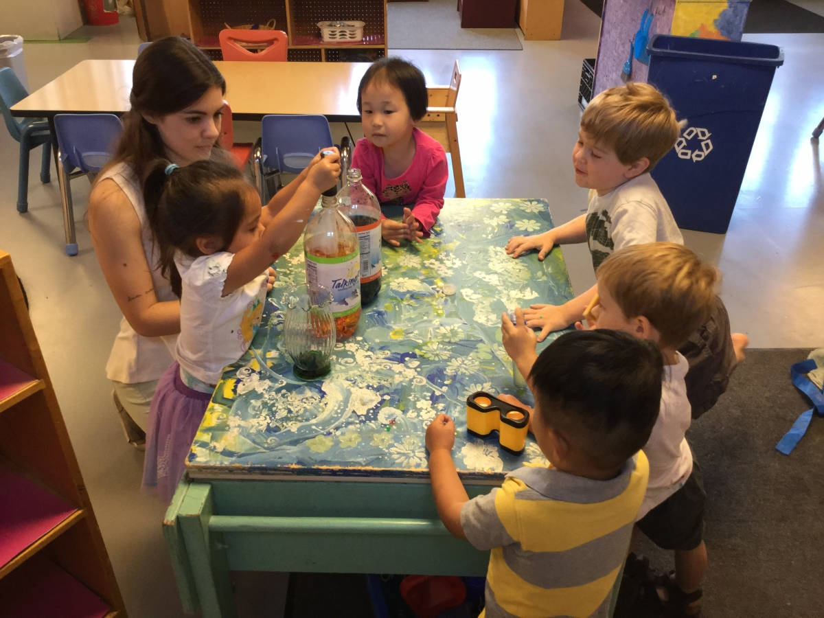 Five children and one adult sitting round a craft table doing an experiment with plastic liter bottles