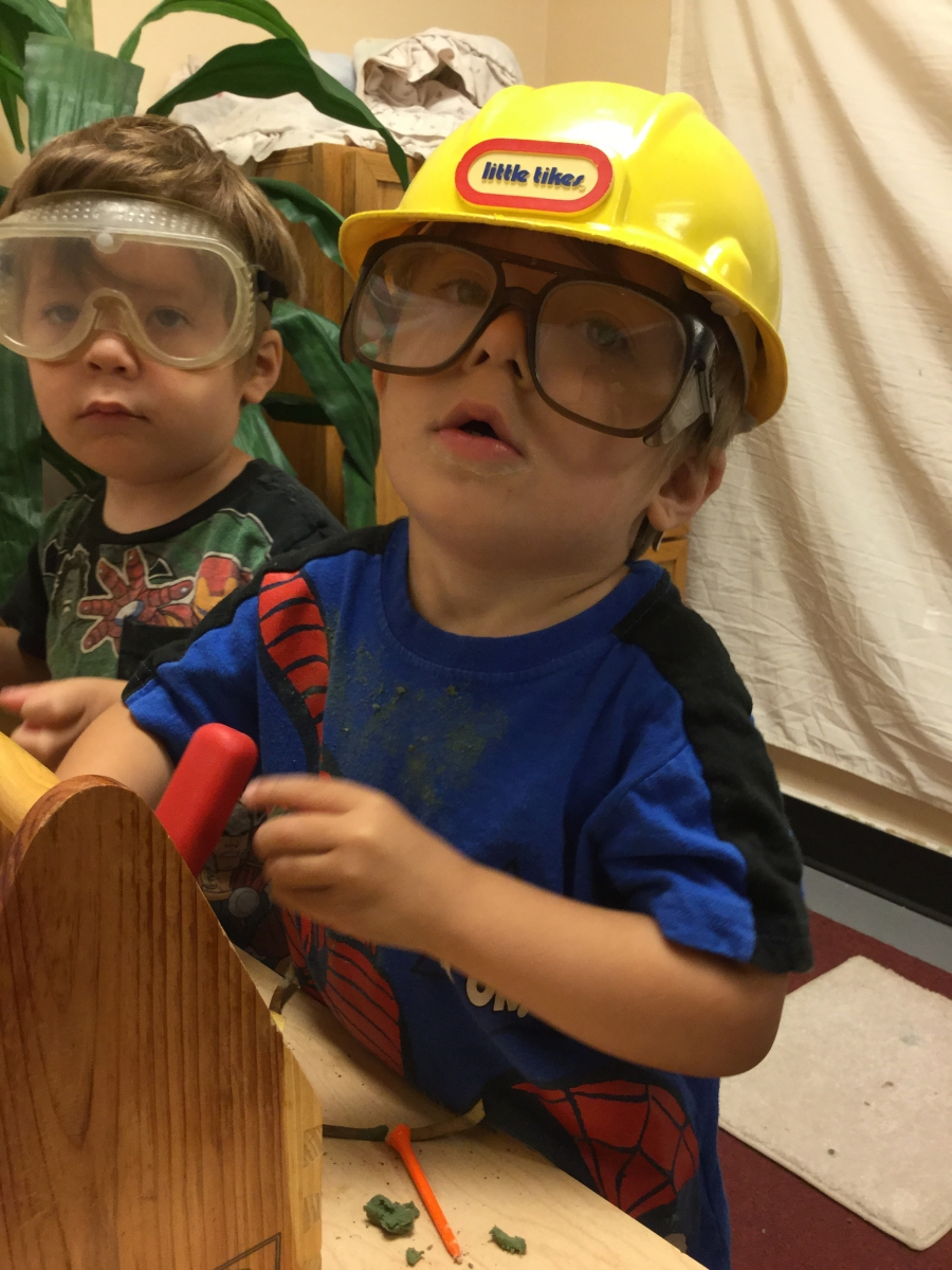 Two young children at a toy workbench, both are wearing safety glasses, on is wearing a hard hat.