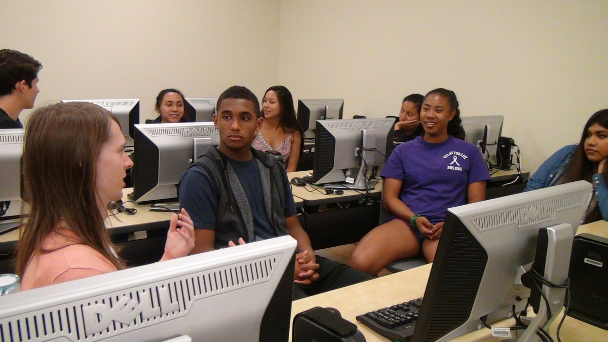 Two rows of students sitting in front of computers. Each group is in conversation.