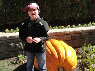 Ethan standing next to a large pumpkin