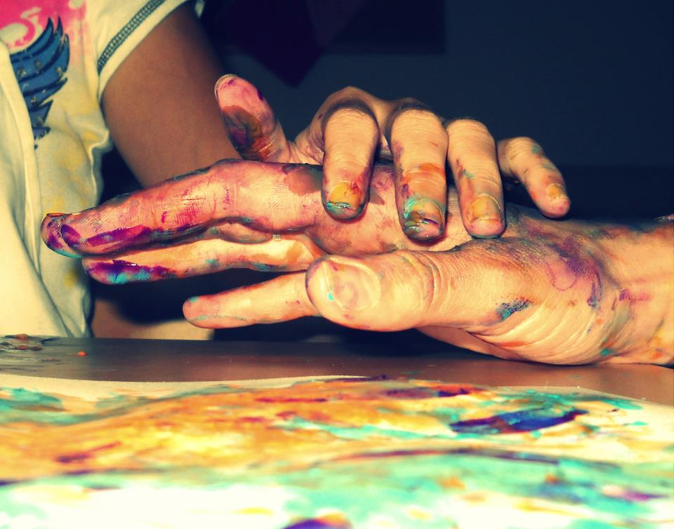 a child's hand and an adult's hand doing fingerpainting