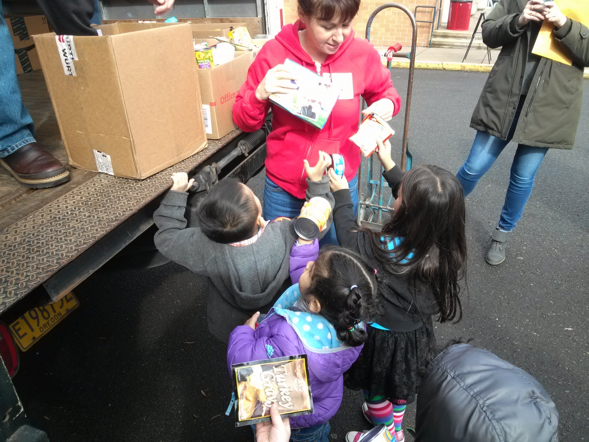 Three children had an adult their food donations while standing at the back of the truck.