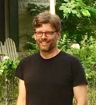 Mike Bicknell, wearing a black T-shirt, stands in front of a background of trees and vines in front of a cream-colored stone house.