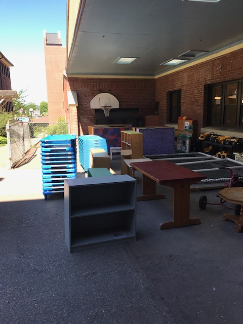 Image description: On the concrete in the Child Development Center's outdoor play area, wooden tables, wooden bookshelves, and stacks of plastic bins sit in the shade of an overhang.