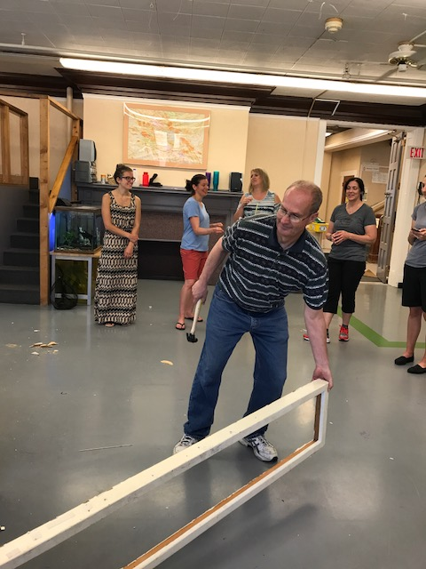 Image description: With one hand, Gary carries the end of a long, white wooden frame. He holds a hammer in the other hand. Behind him, TRI staff members are talking and laughing.