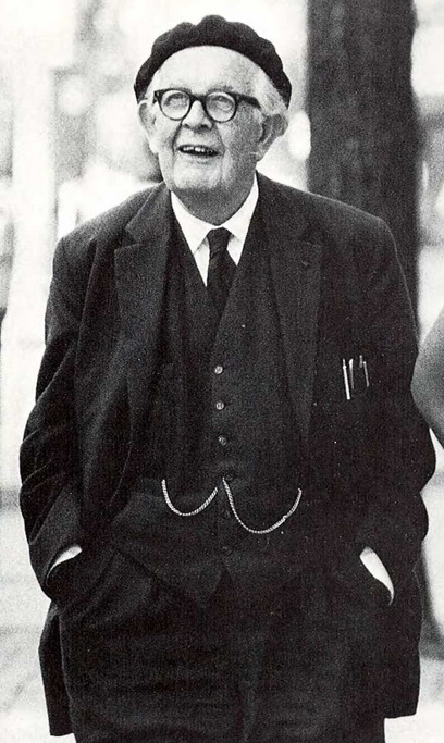 Jean Piaget is standing with his hands in his pockets, wearing a dark 3-piece suit and a black beret. He is at the University of Michigan campus in Ann Arbor - 1968
