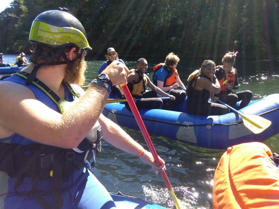 The students are on a river rafting trip. In the foreground is a man with a beard rowing and looking behind him. In the background is a raft full with 5 students, several of whom are smiling at the bearded man.