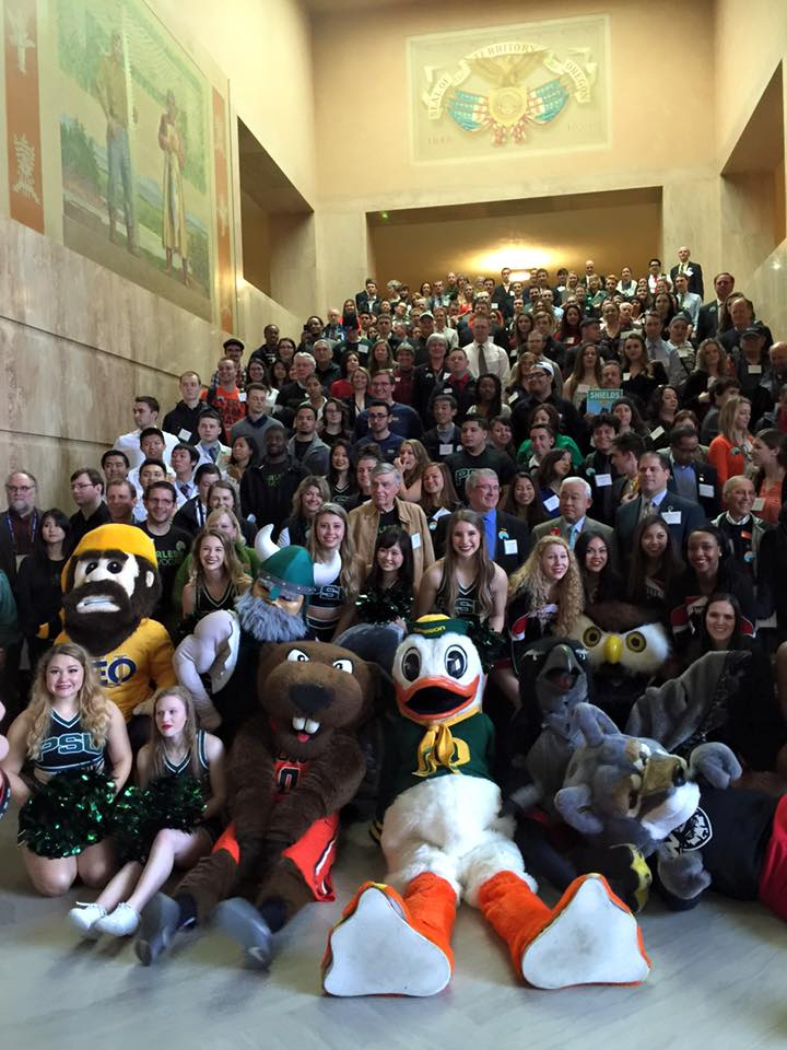 About 200 people sitting on a large staircase. The University mascots and cheerleaders are sitting at the bottom
