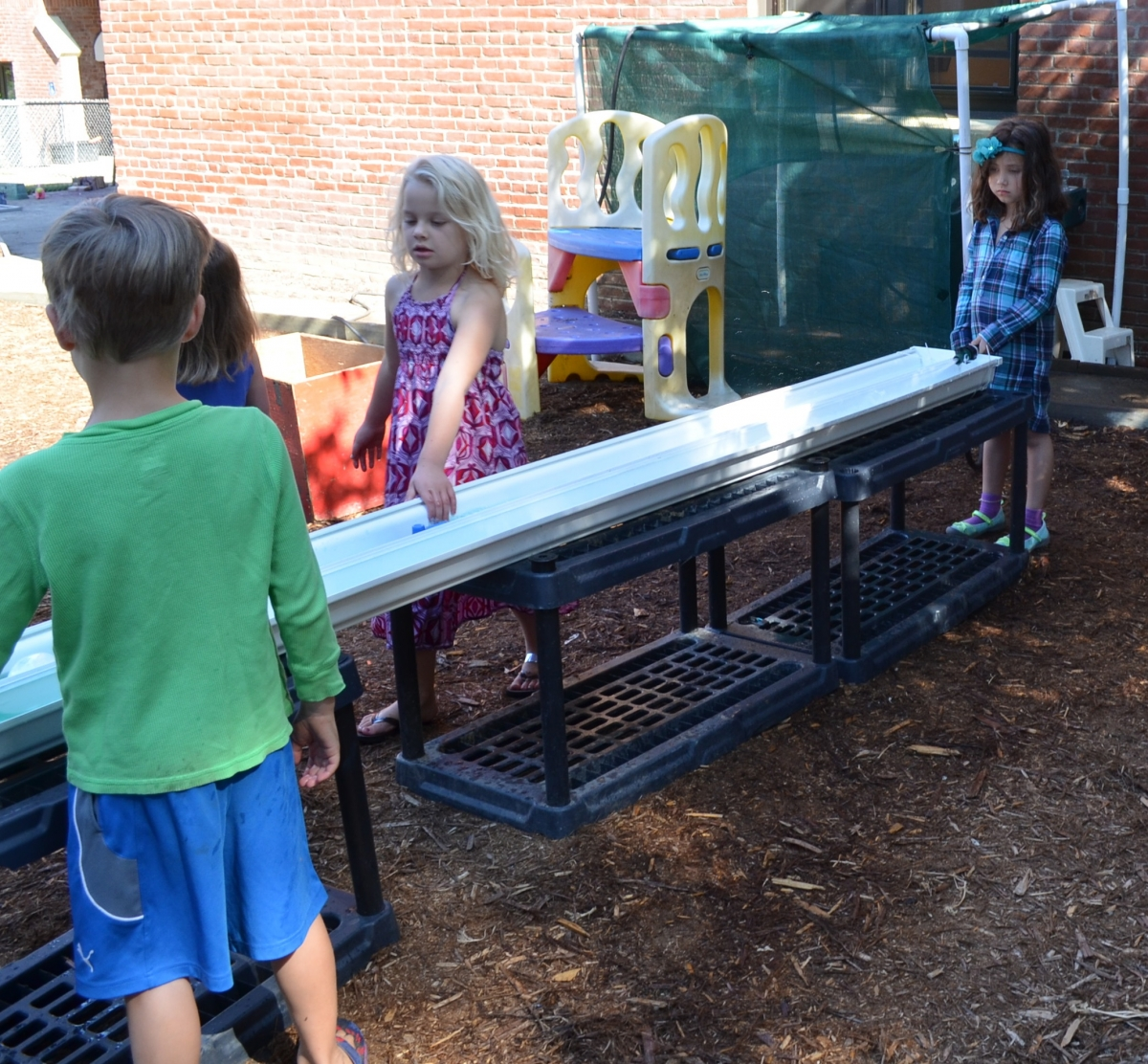 Four children standing outside around a long white plastic trough, playing with water.