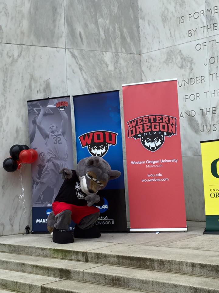 The WOU Mascot crouching in front of several WOU banners