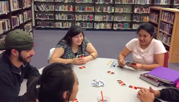 students in library playing card game
