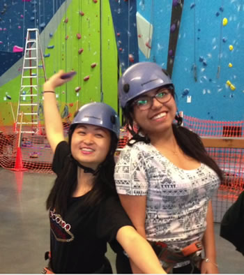 girls posing in front of climbing wall