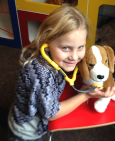 young girl with stethoscope and stuffed dog