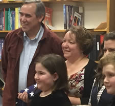Senator Jeff Merkley presenting Faces project director with US flag