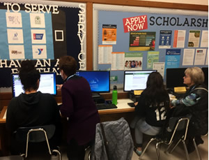 "students sitting at table with adults, bulletin board with text ""to serve"" and ""apply for scholarships"""