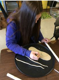 Girl using cutting tool on shoe sole prototype