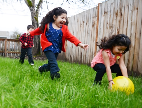 Children playing with ball in grassy yard