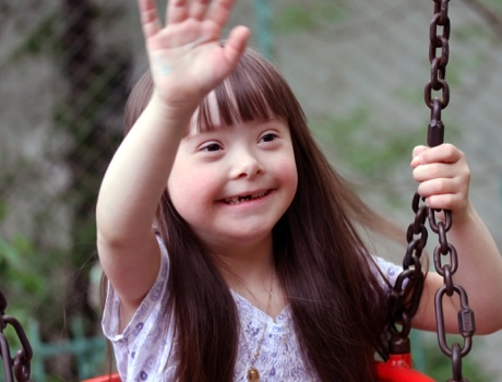 Young girl on swing waving.