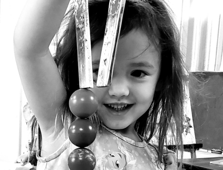 Black and White photo of girl holding a horseshoe magnet.